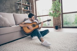 Photo of mixed race guy sitting floor leaning sofa hold acoustic instrumental guitar playing new written song sound signing creative talented person flat loft living room indoors
