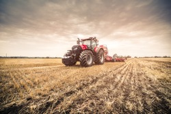 Photo of modern red tractor in the field after harvest seeding directly into the stubble using GPS for precision farming during cloudy summer/autumn day.