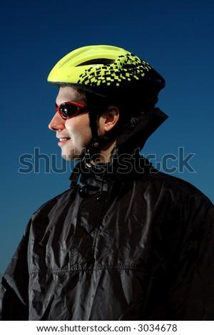 Photo of mountain biker in sporting costume with helmet.