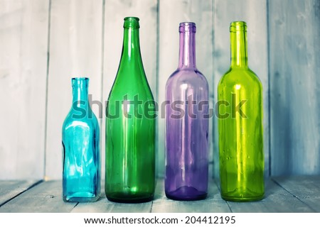 Photo of multi colored bottles on wooden background