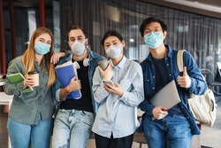 Photo of multinational joyful students in medical masks showing thumb up while standing at classroom