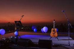 Photo of musical equipment and sunset background. Jazz musician finished show on a skyscraper terrace and put their acoustic guitar and microphones on stage with twilight lighting.