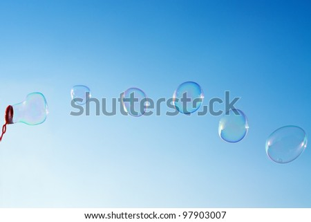 Photo of natural shaped soap bubbles over clear blue sky #97903007