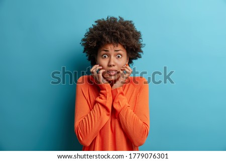 Photo of nervous scared woman grabs face and looks with worried expression at camera, sees phobia, afraids of speaking, wears orange jumper, isolated on blue background. Human reaction concept Photo stock ©
