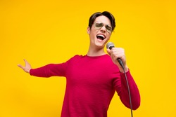 Photo of nice brunet millennial guy sing wear red sweater isolated on yellow color background