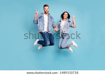 Photo of nice charming cheerful enjoying two people shoiwng you v-sign jumping after having gone on vacation while isolated with blue background
