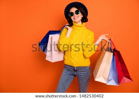 Photo of nice charming girl  attractive joyful girl having just ended up shopping and being overjoyed and cheerful while isolated with orange background