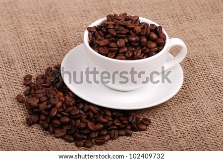 Photo of of cup full of coffee beans on delicious roast coffee beans background/cup full of coffee beans