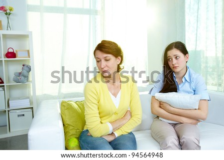 Photo of offended woman sitting on sofa with her teenage daughter being sorry for what she did