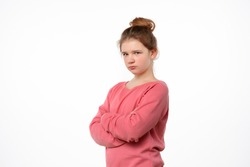 Photo of offended young girl posing isolated on white background. Holding hands crossed, looking at camera. People lifestyle concept