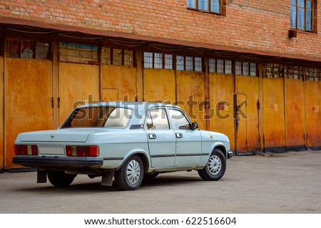 Photo of old classic car standing before rusty gate of building