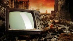 Photo of old fashioned tv set laying on pile of bricks on ruined city wasteland background.