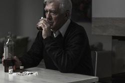 Photo of older sad man drinking alcohol alone