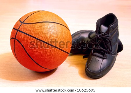 Photo of one basket ball and sneakers in a wooden floor - stock photo