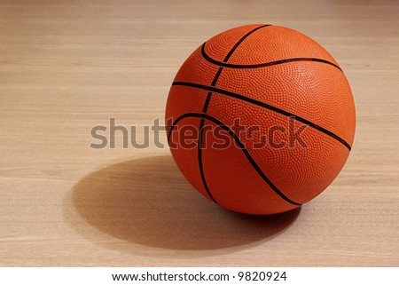 Photo of one basket ball in a wooden floor
