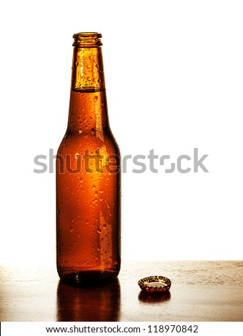 Photo of open beer glass bottle with lid on the table isolated on white background, alcohol beverage, cold bubbles drink, amber ale, brew pub, german beer festival, tavern, fresh lager