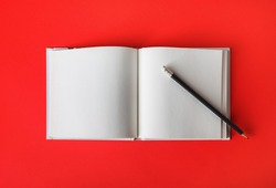 Photo of open book with blank pages and pencil on red paper background. Responsive design template. Flat lay.