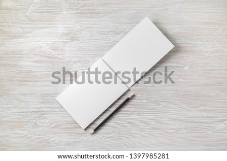 Photo of open sketchbook with blank pages and pencil on light wood table background. Responsive design template. Flat lay.