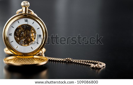 Photo of opened old vintage pocket clock against the black background