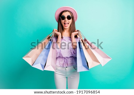 Photo of optimistic brunette girl hold bags open mouth wear purple shirt cap trousers spectacles isolated on blue color background
