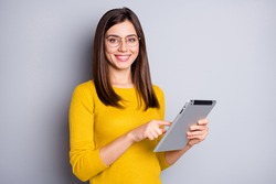 Photo of optimistic brunette nice lady hold tablet wear eyewear yellow sweater isolated on grey color background