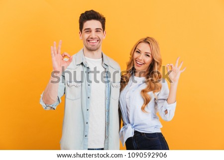 Photo of optimistic people man and woman in basic clothing smiling and gesturing ok symbol at camera isolated over yellow background