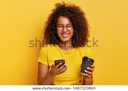 Photo of overemeotive relaxed dark haired female holds takeout cup of cappuccino, views funny photos from party online, uses modern electronic gadget, makes video conference, dressed casually