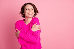 Photo of overjoyed lady hands hug herself shoulders enjoy joyful soft cloth laundry warmth toothy smile look empty space wear casual bright sweater isolated pink pastel color background
