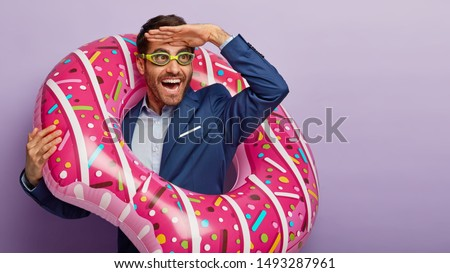 Photo of overjoyed male office worker focused into distance, keeps palm near forehead, pretends being on beach, wears goggles for swimming, poses in inflated swimring, notices something funny