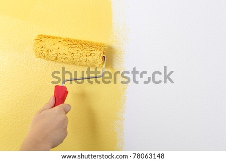 Photo of painting a wall with a roller and yellow paint.