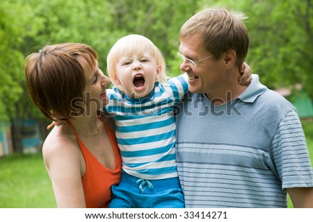 Photo of parents holding son screaming on camera
