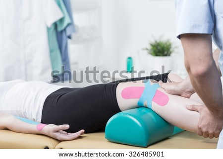 Photo of patient with elastic therapeutic tape during exercises