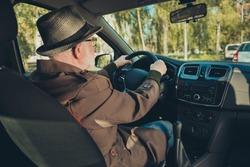 Photo of pensioner grandpa drive sit seat look roadway hold steering wheel wear brown jacket cap specs inside car