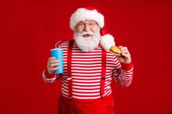Photo of pensioner grandpa grey beard hold cup soda burger retail remote order restaurant wear santa costume suspenders spectacles striped shirt headwear isolated red color background