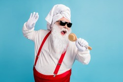 Photo of pensioner old fat man grey beard hold body brush sing shower pretend hold mic play funny game wear santa x-mas costume towel turban suspender sunglass isolated blue color background