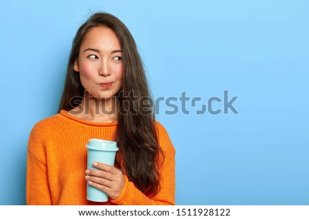 Photo of pensive brunette woman purses lips, looks thoughtfully aside, holds takeout coffee, makes decision in mind, plans her day, wears orange jumper, stands over blue wall. Asian girl with beverage
