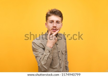 Photo of pensive nerd in shirt and glasses against yellow background, looks into camera with serious face and thinks. Funny thoughtful guy isolated on a yellow background. Copy space