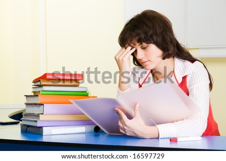 Photo of pensive teacher sitting at the desk and refreshing study material before lesson