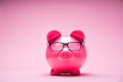 Photo Of Piggybank Wearing Glasses On Pink Background