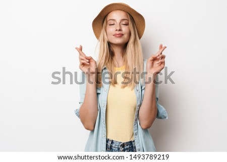 Photo of pleased amazing young pretty woman wearing hat posing isolated over white wall background make hopeful please gesture.