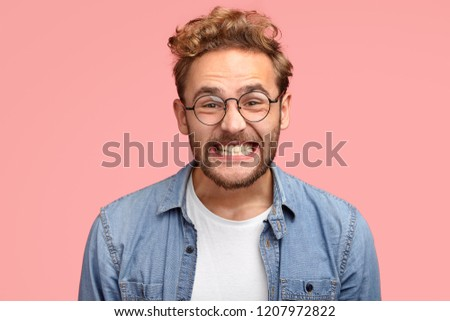 Photo of pleased curly Caucasian man smiles joyfully at camera, clenches teeth, dressed in fashionable blue shirt, being in good mood after date with girlfriend, poses against pink background