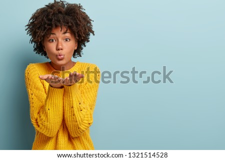 Photo of pleased dark skinned woman has Afro haircut, stretches hands near face, blows air kiss, expresses love and affection, isolated over blue background, free space aside for your promotion #1321514528