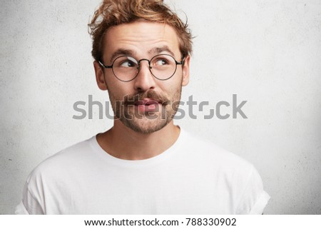 Photo of pleased dreamy male wonk with trendy hairdo, wears spectacles and casual white t shirt, imagines something pleasant, looks upwards with intriguing expression, isolated on concrete wall #788330902