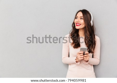 Photo of pleased female smiling looking aside with silver smartphone in hands enjoying favorite music, via wireless headphones over gray background