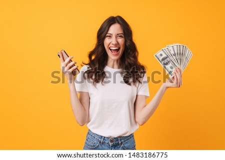 Photo of pleased happy screaming young woman posing isolated over yellow wall background using mobile phone holding money.