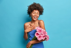 Photo of pleased sincere dark skinned woman smiles pleasantly holds beautiful bouquet of gerbera flowers wears dress isolated over blue background. Spring female has festive mood. 8 March concept