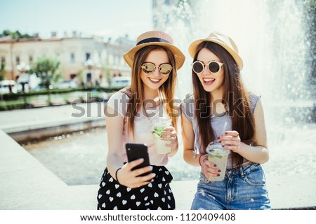 Photo of pleased two mixed race women get good news on mobile phone, recieve email or make selfie with smart phone, drink fresh cocktails outdoors. Interracial friendship and recreation time concept