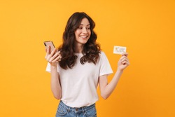 Photo of pleased young woman posing isolated over yellow wall background using mobile phone holding debit card.