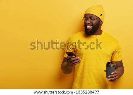 Photo of plump black man in stylish yellow hat and t shirt, sends funny meme on cell phone, holds takeaway coffee, has nice talk in social networks, connected to wireless internet, enjoys spare time