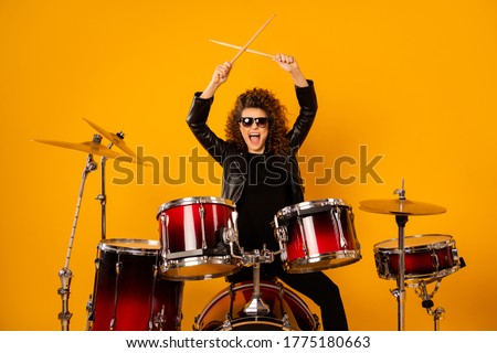 Photo of  Photo of popular rocker redhair lady plays instruments beat raise hands drum sticks concert sound check repetition wear black leather outfit sun glasses isolated yellow background